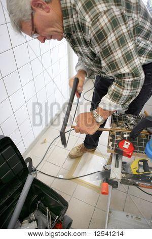 A senior man sawing a pipe in metal