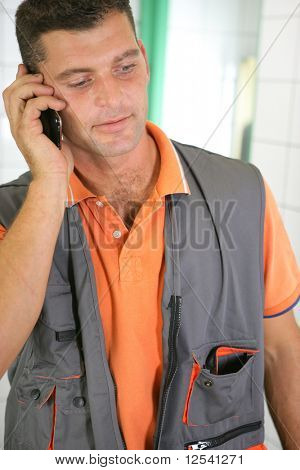 Portrait of a plumber phoning