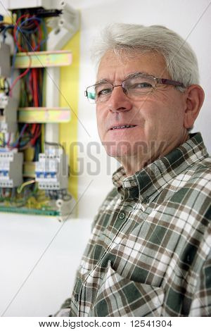 Portrait of a man next to an electric meter
