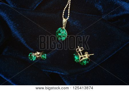 Feminine accessories: emerald pendant and earrings on velvet