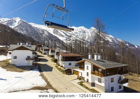 ROSA KHUTOR, RUSSIA - APRIL 01, 2016: Mountain ski resort Rosa Khutor with cottages on snowy mountains background