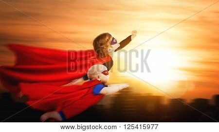 children superheroes flying across sunset sky. boy and girl brother and sister