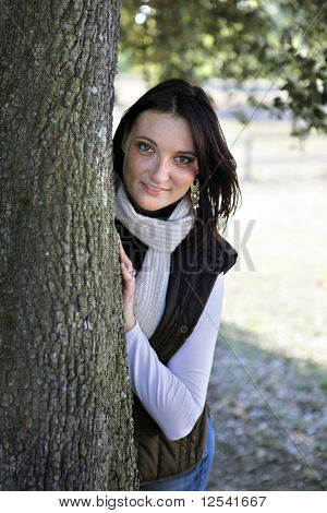 Portrait of a smiling young woman hidden behind a tree