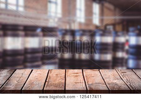 Wooden table against stacks of beer barrels
