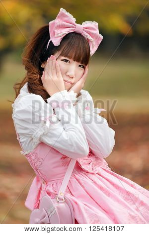 Portrait of Japanese in sweet lolita cosplay holding his head
