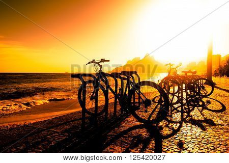 Parked Bicycles in Ipanema Beach by Sunset