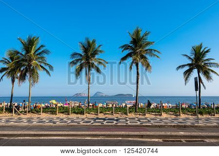Rio de Janeiro, Brazil - April 9, 2016: Sidewalk with palm trees in Ipanema beach. The beach gets full of people during weekends.