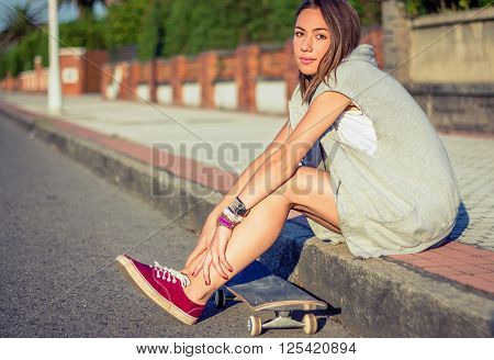 Portrait of beautiful young girl with short shorts and skateboard sitting outdoors on a hot summer day. Warm tones edition.