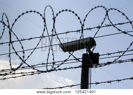Security Camera Behind Barbed Wire Fence Stretched Around Prison Walls