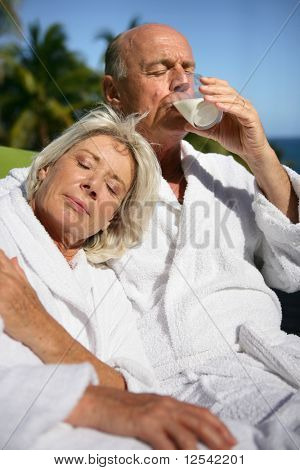 Portrait of a senior woman and a senior man drinking a glass of water