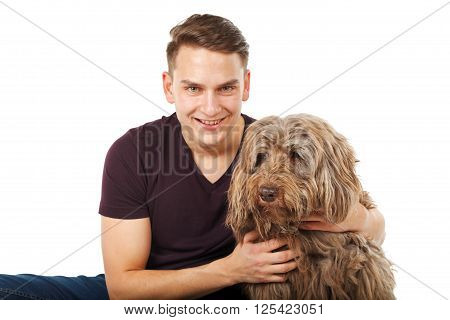 Young man sitting with his furry brown dog