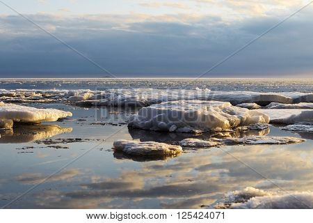 blocks of ice are thawing on the sunset lights in the spring evening
