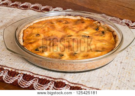 Cake with cottage cheese and prunes in glass brazier on wood table.