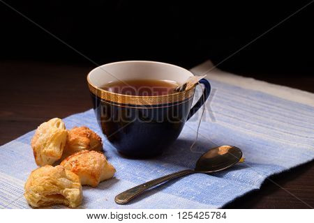 Cup of tea with a bag of tea leaves and home-made cookies. On a napkin from fabric a dark background style of negligent tea drinking