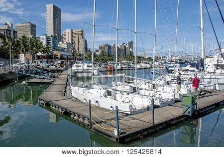 Wooden Walkway And Yachts Against City Skyline