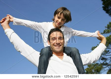 Portrait of a little boy sitting on the shoulders of a man