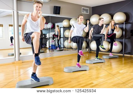 Focused and dedicated people in team raises legs at step platform in a fitness gym class. Stamina and body coordination workout. Teamwork and motivation.