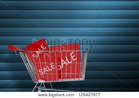 Trolley with sale shopping bags against grey shutters