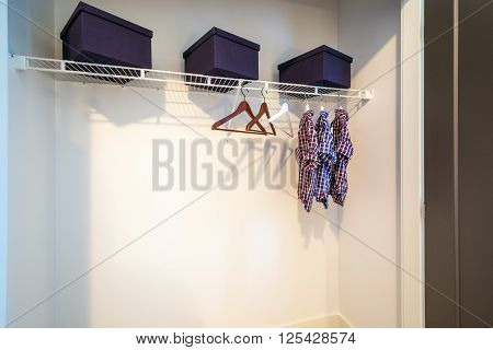 Boys closet with dress shirts and hangers.