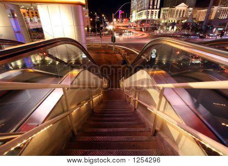 Escaleras mecánicas y escaleras abajo con tráfico borrosa y luces