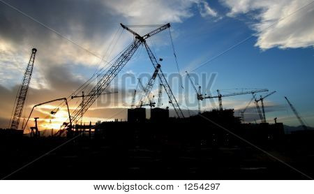 Construction Site Sillouhette With Multiple Cranes At Sunset