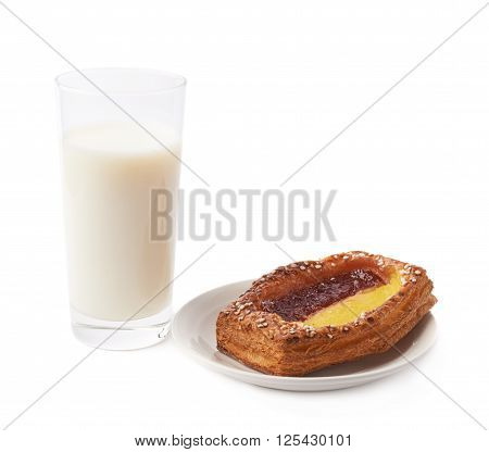 Sweet bread bun pastry filled and covered with the red and yellow cream filling in a white ceramic plate next to glass of milk, isolated over the white background