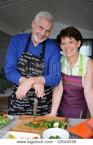 Portrait of a smiling senior couple with aprons of cooking
