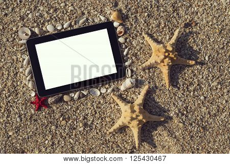 Photo frame made of seashells and pebbles with two starfish placed next to it and tablet computer within the frame with blank screen on the beach