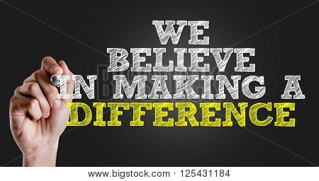 Hand writing the text: We Believe in Making a Difference