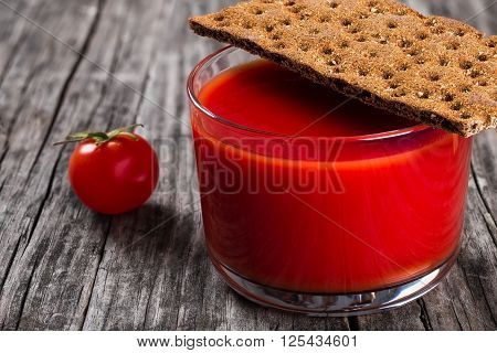 fresh tomato juice in a glass on a wooden table with wholegrain crispbread close up