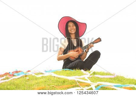 Pretty Asian young  woman sit on mound playing Ukulele.