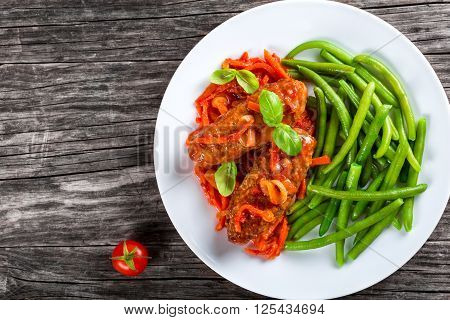 Delicious Meat Cutlets stewed with onion carrot tomato sauce decorated with basil leaves in a white dish with boiled green bean top view