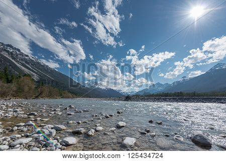 stone bank at flowing river lech in tirol lechtal aith blue sky and sun