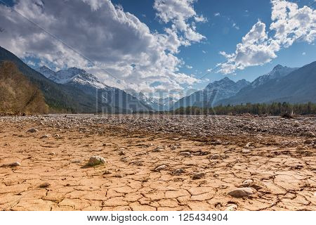 dry cracked earth ground with stones in mountain land at blue sky