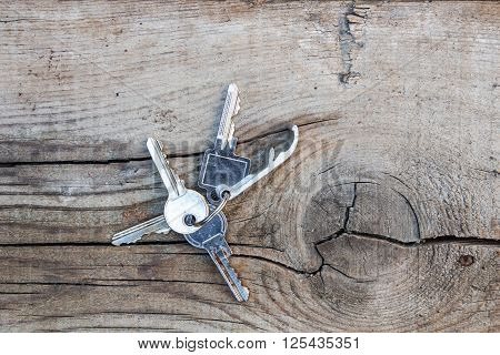 Set of metal keys on a old cracked wooden background
