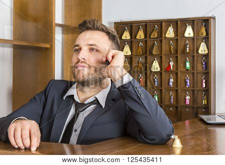 Portrait of a serious receptionist on the phone at his desk in a small hotel.