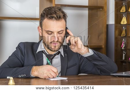 Portrait of a receptionist taking notice on a piece of paper while he is on the phone at his desk in a small hotel.
