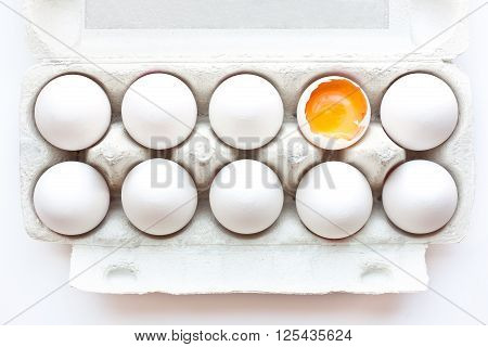 Broken egg in a carton box isolated in white background