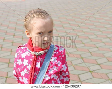 Portrait of small pensive Caucasian schoolgirl in a pink jacket on the square paved with colored tiles