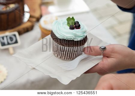 spongecake or muffin with cream in hand
