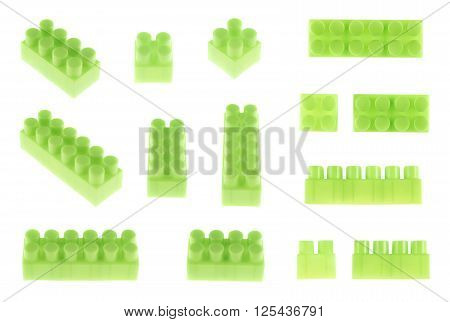 Set of plastic green toy construction block bricks in multiple foreshortenings, isolated over the white background
