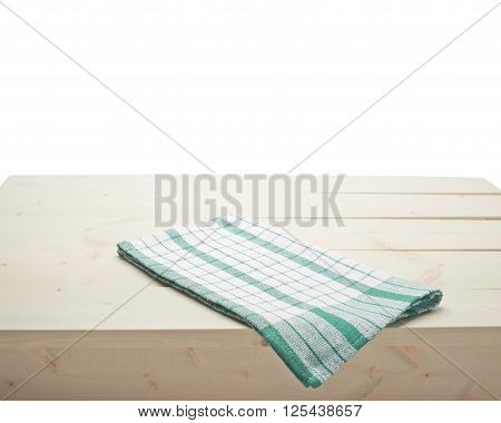 Green squared tablecloth or towel over the surface of a wooden table, composition isolated against the white background