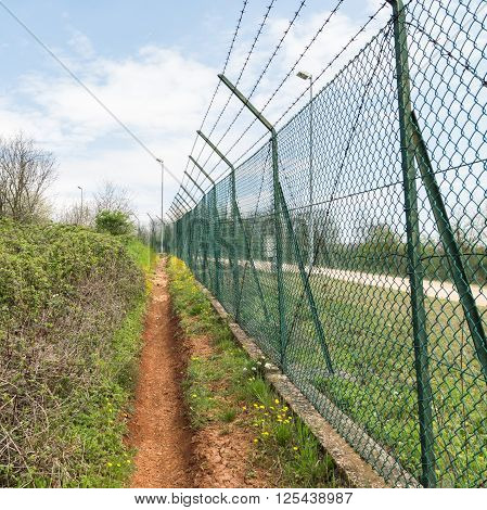 Green mesh fence topped with barbed wire.