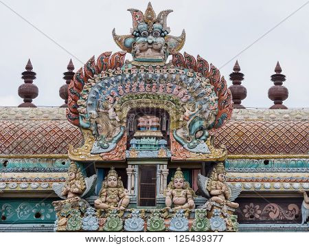 Trichy India - October 15 2013: Closeup of bow decoration on the Vimanam of one Gopuram at Shirangam temple. Monster face on top of pastel-colored highly decorated bow showing small humans elephants horses parrots dog-like animals.