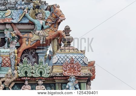 Trichy India - October 15 2013: Closeup of decoration on one Gopuram at Shirangam temple. Fighting man on brown horse seems to jump off the temple. Pastel colors gray sky.