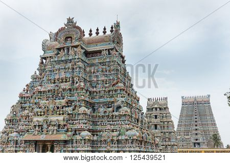 Trichy India - October 15 2013: Three of the twenty-one gopurams in a row at the Shirangam Vishnu temple. Hundreds of statues. Pastel colors against a gray sky which is broken open by blues.