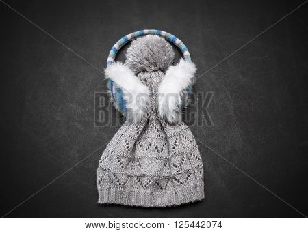 Nice amazing closeup view of knighted girl's stylish light grey winter hat with earmuffs on dark background