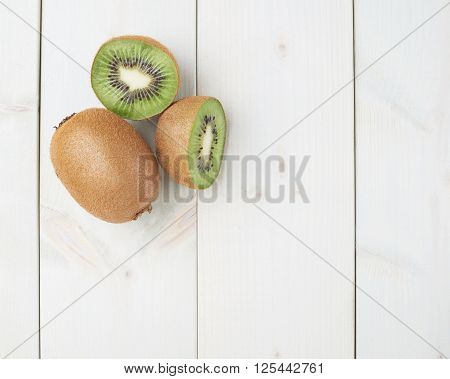 Two sliced kiwifruits or chinese gooseberry kiwi fruits composition over the white wooden boards surface