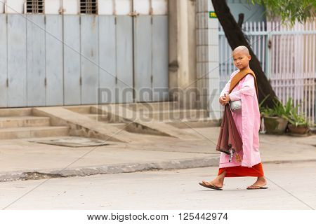 MANDALAY,MYANMAR,JANUARY 17, 2015: A young Buddhist nuns is walking in the streets of Mandalay, Myanmar (Burma).