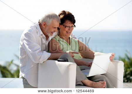 Portrait of a senior couple smiling in front of a laptop